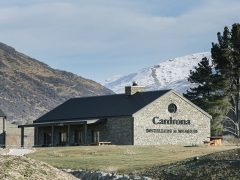 Cardrona Distillery and Museum exterior building with mountains in distance