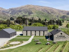 Cardrona Distillery and Museum three schist buildings on lawn and hills in background
