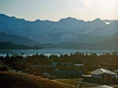 View over Lake Wanaka and snowy mountains with Holy Family Catholic Church in foreground