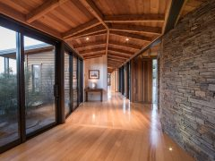 Buchanan Rise House interior hallway timber floor and ceiling with schist walls