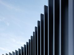 Wanaka Community Hub exterior curved black vertical louvres with blue sky