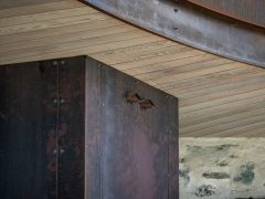 Saddle house exterior curved soffit detail showing corten steel