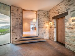 Saddle house interior entranceway and foyer with tiles and schist stone walls