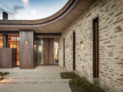 Saddle house exterior curved roofline schist stone wall