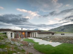 Saddle house exterior house with landscaped lawn and pathways