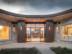 Saddle house exterior curved roofline looking into living space