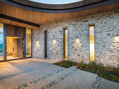 Saddle house exterior entrance way paved path and schist cladding