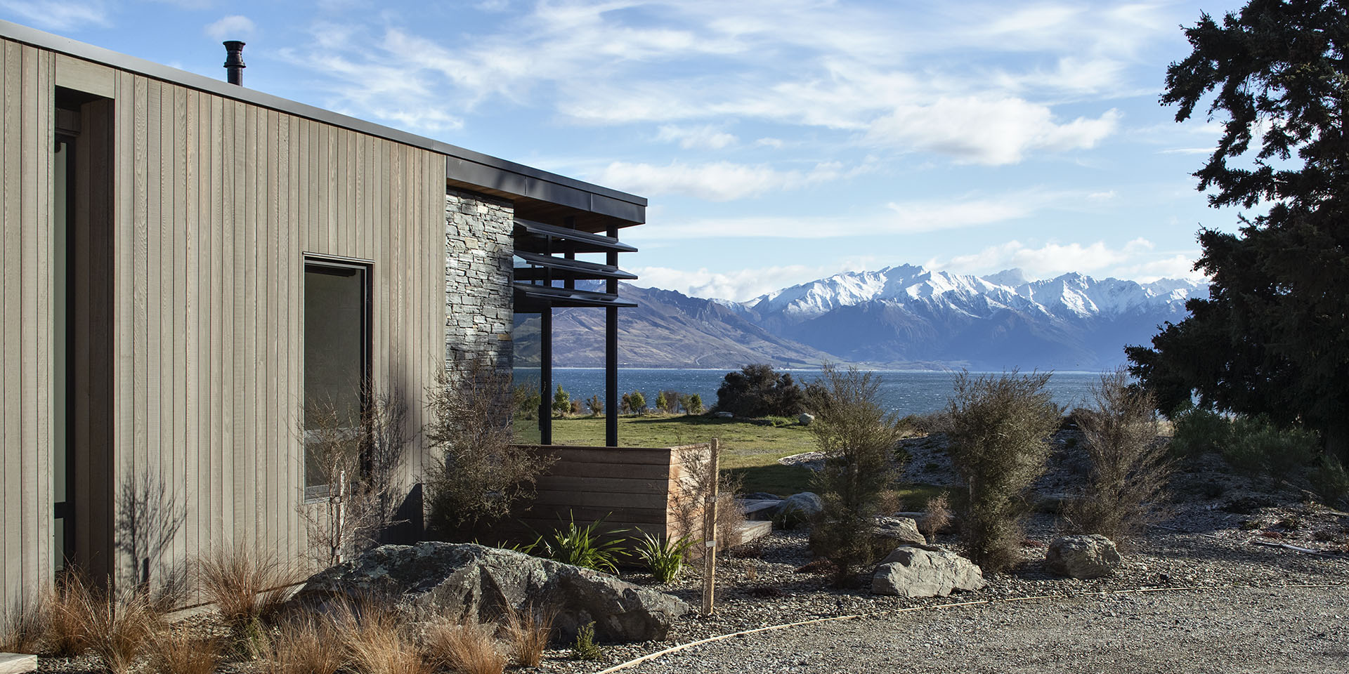 Lake Hawea House exterior side of house with cedar cladding looking over lake and mountains