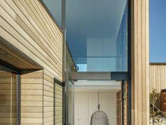 Bargour Residence exterior house with cedar cladding looking through window to interior