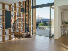 Bargour Residence interior floor to ceiling library shelving with hanging chair